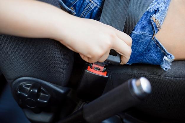 Nahaufnahme der frau, die sicherheitsgurt des sitzes im auto vor abfahrt befestigt