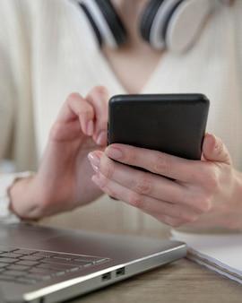Nahaufnahme der frau, die smartphone neben laptop verwendet