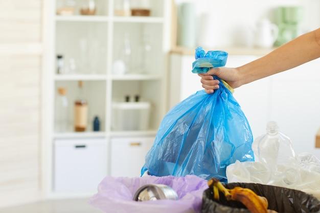 Nahaufnahme der frau, die tasche mit müll in den mülleimer wirft, während hausarbeit zu hause