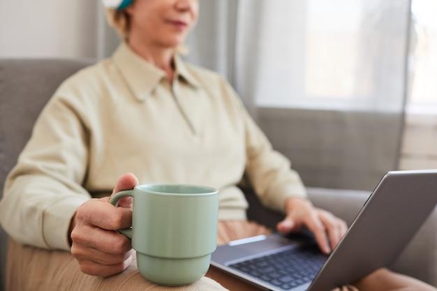 Nahaufnahme der frau, die tasse kaffee hält, während auf sofa mit laptop sitzen und kaffee am morgen trinkt