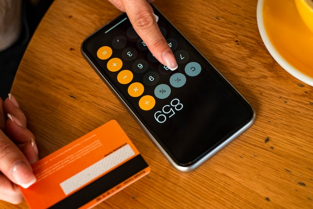 Nahaufnahme der frau, die unter verwendung der kreditkarte und des mobilen smartphone-rechners zahlt und einkauft