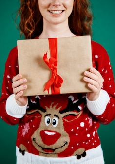 Nahaufnahme der frau, die weihnachtsgeschenk hält