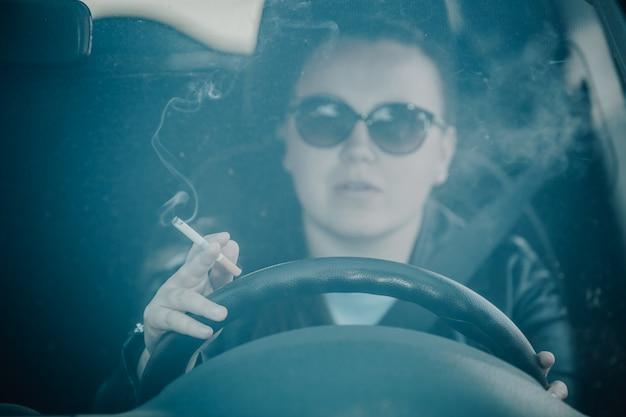 Nahaufnahme der frau, die zigarette im auto raucht, während sie ein fahrzeug fährt, drohendes und gefährliches fahren, fokus auf hand