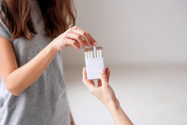 Nahaufnahme der frau, die zigarettenpackung hält und einer anderen person zigarette vorschlägt