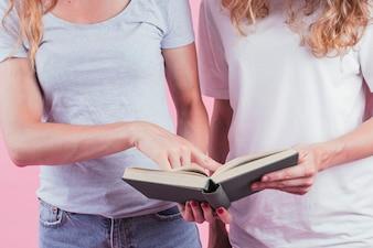 Nahaufnahme der Frau Finger auf Bucheinfluß durch ihren Freund zeigend