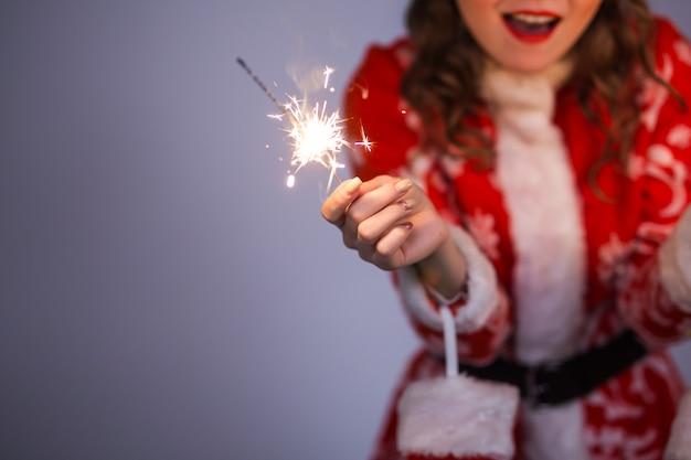 Nahaufnahme der frau im roten weihnachtsmantel und im hut, die wunderkerze halten