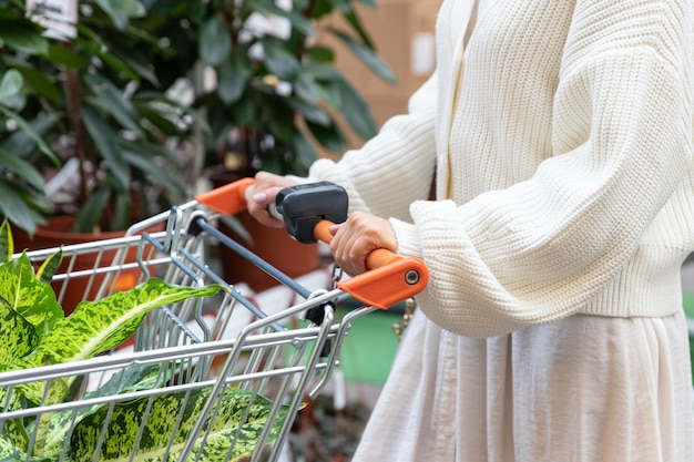 Nahaufnahme der frau im weißen pullover mit einkaufswagen, der pflanzen für ihr haus im gewächshaus oder im gartencenter auswählt und kauft