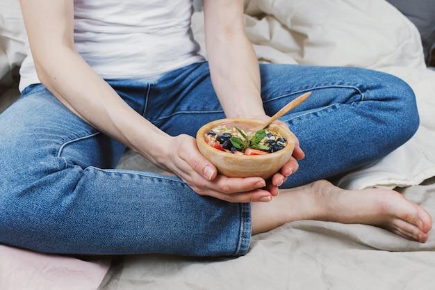 Nahaufnahme der frau in den jeans und im weißen hemd in ihrem bett, das vegane smoothie-schüssel hält