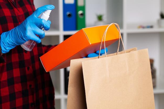 Nahaufnahme der frau in den schutzhandschuhen, die einkaufen desinfizieren