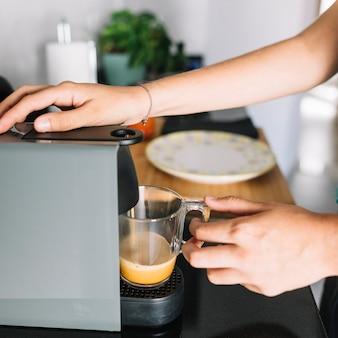 Nahaufnahme der Frau Kaffee von der Kaffeemaschine nehmend