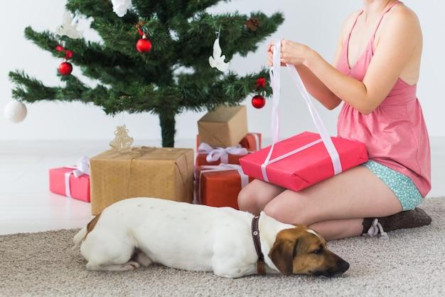 Nahaufnahme der frau mit dem hund, der weihnachtsgeschenke öffnet. weihnachtsbaum mit geschenken darunter. dekoriertes wohnzimmer