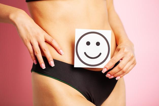 Nahaufnahme der frau mit der schlanken figur, die nahe bauchkarte mit lächelndem lächeln hält