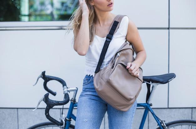 Nahaufnahme der frau mit ihrem rucksack, der auf fahrrad sich lehnt