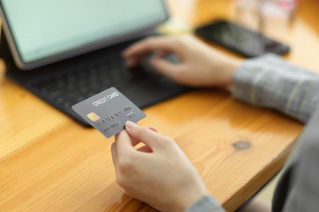 Nahaufnahme der frau mit kreditkarte und tablet mit leerem bildschirm für online-zahlungen e-commerce