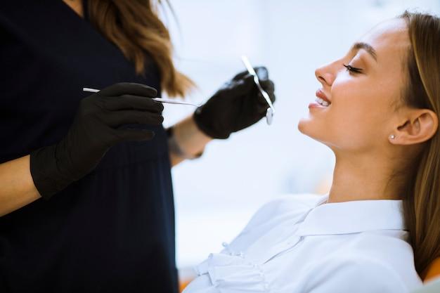 Nahaufnahme der frau mit offenem mund während der mündlichen überprüfung am zahnarzt