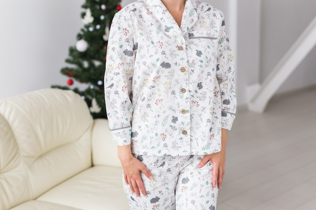Nahaufnahme der frau mit pyjama im wohnzimmer mit weihnachtsbaum. urlaub konzept.