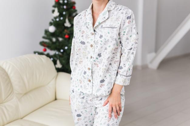 Nahaufnahme der frau mit pyjama mit schönem hund im wohnzimmer mit weihnachtsbaum. urlaub konzept.