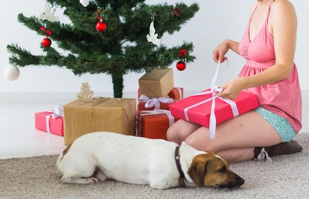 Nahaufnahme der frau mit schönem hund, der geschenkbox unter weihnachtsbaum öffnet. urlaub konzept.