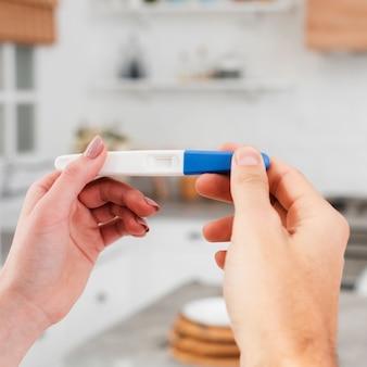 Nahaufnahme der frau schwangerschaftstest halten