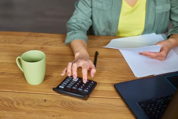 Nahaufnahme der frau sitzen, berechnen die ausgaben auf dem taschenrechner am holztisch, moderner arbeitsplatz, freiberufler, der zu hause arbeitet. frauen, die beschäftigt sind, verwalten die ausgaben für das familienbudget.