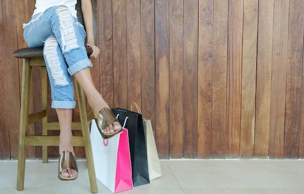 Nahaufnahme der frau sitzend mit einkaufstaschen und kopienraum