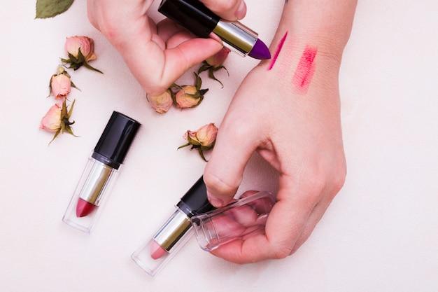 Nahaufnahme der frau verschiedene lippenstifte an hand über weißem hintergrund prüfend