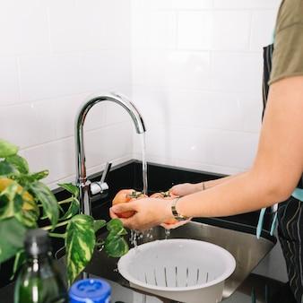 Nahaufnahme der frau waschende tomaten in der wanne
