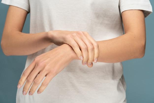Nahaufnahme der frauenarme, die ihr schmerzhaftes handgelenk halten, verursacht durch längere arbeit am computer