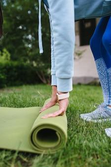 Nahaufnahme der frauenfalzrollenfitness oder der yogamatte nach dem training im park