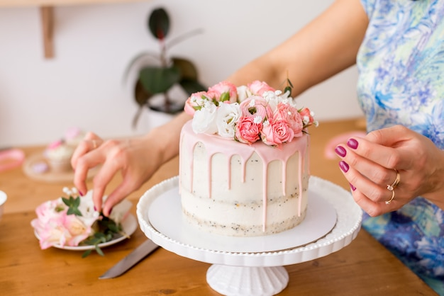 Nahaufnahme der frauenhände, die den kuchen mit frischen blumen verzieren.