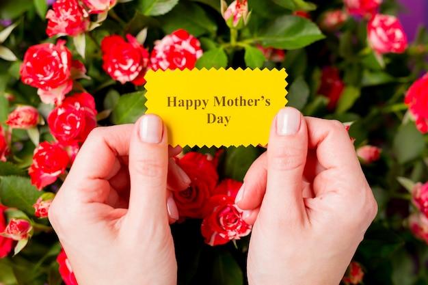 Nahaufnahme der frauenhände, die grußkarte mit glücklichem muttertag des textes und schönem blumenstrauß der rosa roten rosensprührosenblumen halten. muttertagskonzept.