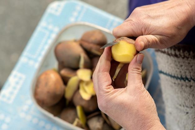 Nahaufnahme der frauenhände, die kartoffeln mit einem küchenmesser schälen.