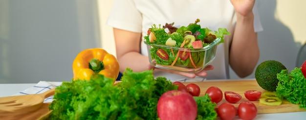 Nahaufnahme der frauenhände, die salatschüssel und verschiedene grünes blattgemüse auf dem tisch am haus zeigen.