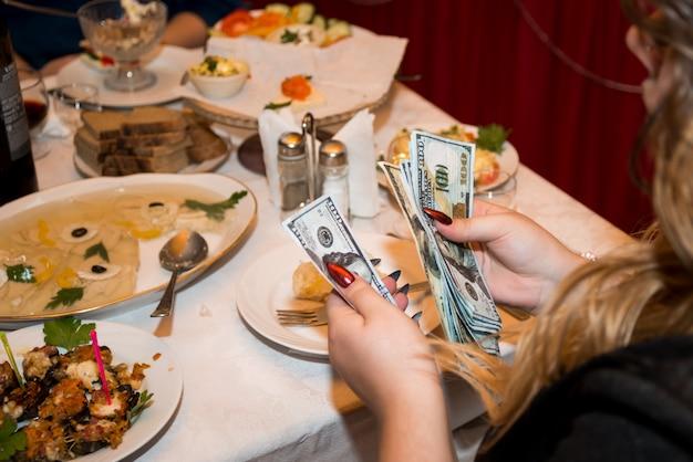 Nahaufnahme der frauenhände mit einer hellen maniküre, die geld-us-dollar zählt, in einem restaurant