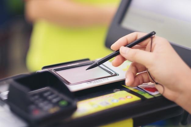 Nahaufnahme der frauenhand des verbrauchers, die auf einem touch screen der kreditkarte unterzeichnet