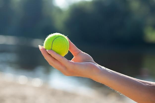 Nahaufnahme der frauenhand, die tennisball am strand hält. freiraum
