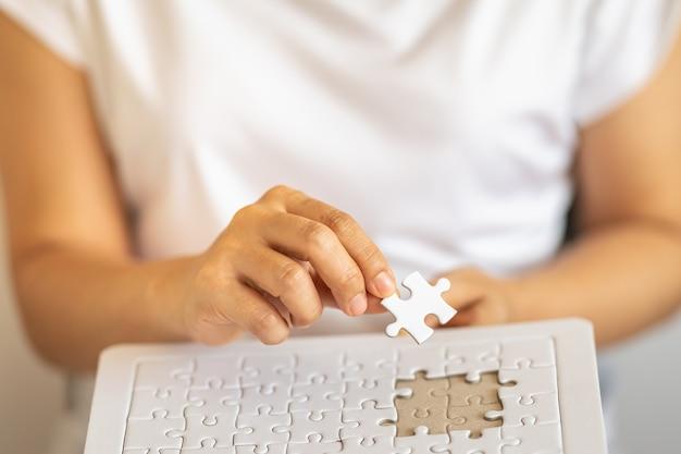 Nahaufnahme der frauenhand, die weißes papierpuzzle hält und niederlegt, um rätsel zu lösen.