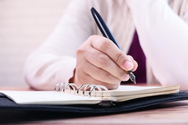 Nahaufnahme der frauenhand mit füllfederhalter, der auf notizblock schreibt.