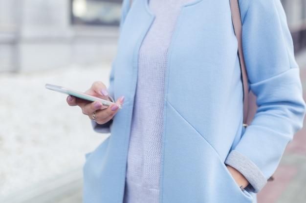Nahaufnahme der frauenhand mit handy oder lesen von nachrichten vom smartphone am morgen