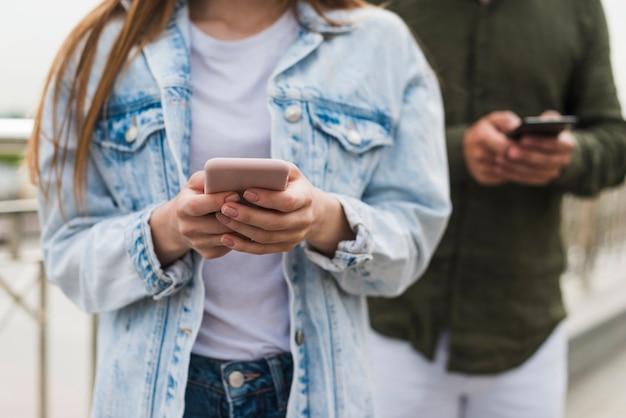 Nahaufnahme der frauenhand unter verwendung des mobiltelefons