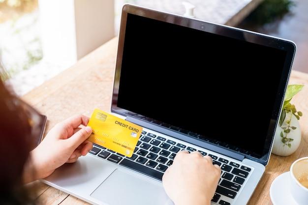 Nahaufnahme der freiberuflichen hand der weiblichen geschäftshand, die kreditkarten hält, die lässig mit laptop arbeiten