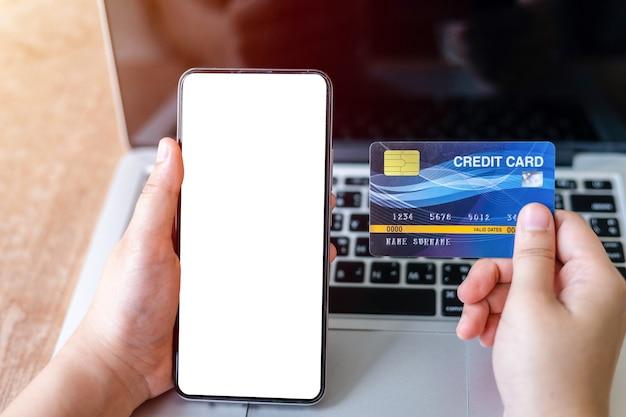 Nahaufnahme der freiberuflichen hand der weiblichen geschäftshand, die kreditkarten lässig und smartphone hält, die mit laptop arbeiten