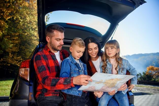 Nahaufnahme der freudigen angenehmen familie, die in ihrem urlaub mit jugendlichen kindern zusammenkommt und straßenkarte verwendet, um den richtigen weg auf dem auto zu wählen