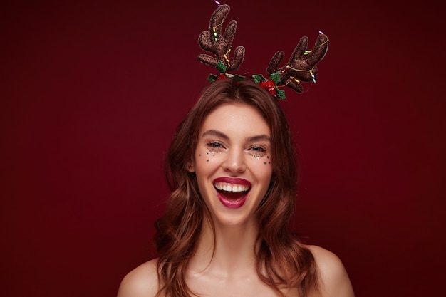 Nahaufnahme der freudigen attraktiven jungen brünetten dame mit gewellter frisur, die feiertagshörner auf weihnachtsfeier trägt, sich im stehen freuend, wahre positive gefühle ausdrückend