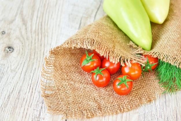 Nahaufnahme der frisch eingelegten ernte von gemüse - paprika, bohrer und tomaten auf holztisch. rustikaler stil. bio-konzept für gesunde lebensmittel mit kopierraum
