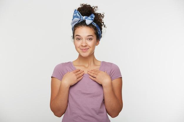 Nahaufnahme der fröhlichen schönen brünetten jungen frau mit dem stirnband trägt rosa t-shirt sieht freudig aus und zeigt auf sich