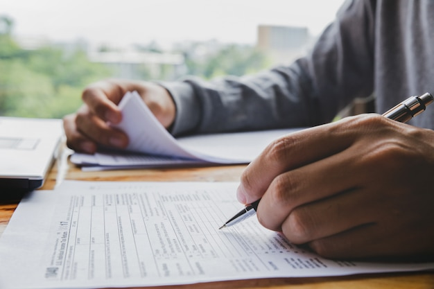 Nahaufnahme der füllenden einkommenssteuerformen der mannhand