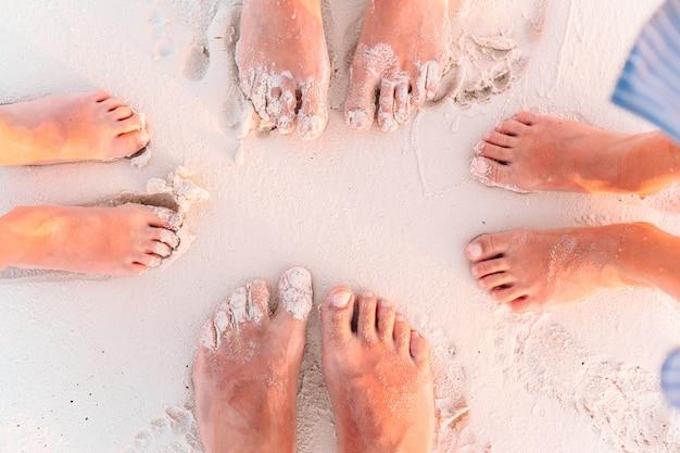 Nahaufnahme der füße der familie am weißen sandstrand