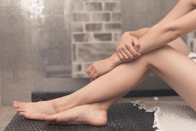 Nahaufnahme der füße der frau, die auf klubsessel im badekurort sich entspannen