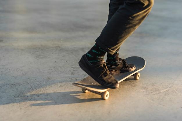 Nahaufnahme der füße, die mit dem skateboard üben